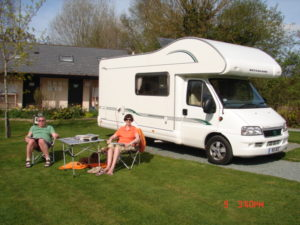 A couple relaxing outside their motor home at daisy bank