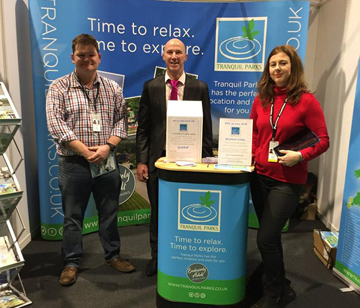 Mark from Daisy Bank Touring Caravan Park, James from The Old Oaks and Vicki from Back of Beyond on the Tranquil Parks stand at the Birmingham NEC show, February 2018
